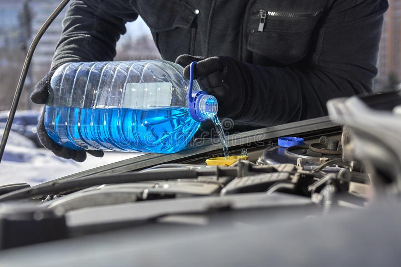 Man pouring an antifreeze liquid in a windshield washer tank of a car stock images