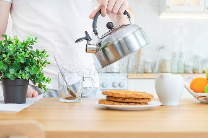Man pouring boiling water from kettle into a cup with instant coffee. Morning coffee or making breakfast in the kitchen. Man pouring boiling water from metal stock image