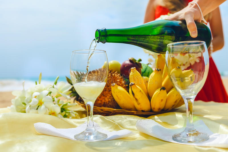 Man is pouring champagne into a glass on a background of a plate with fruit. Celebration on the beach. Close-up stock photos