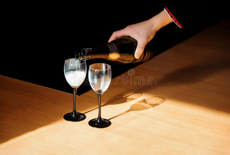 A man pouring champagne into a glass on some festive event or wedding reception stock image