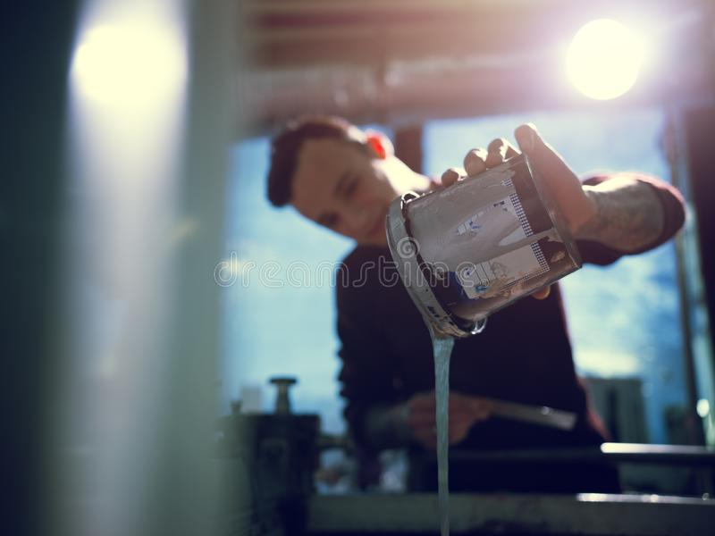Man pouring container with silver color in workshop royalty free stock photos