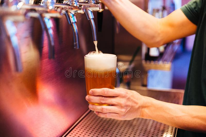 Man pouring craft beer from beer taps in frozen glass with froth. Selective focus. Alcohol concept. Vintage style. Beer craft. Bar table. Steel taps. Shiny royalty free stock images