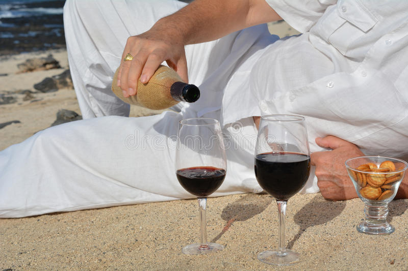 Man pouring red wine from bottle into a glass on the beach royalty free stock images