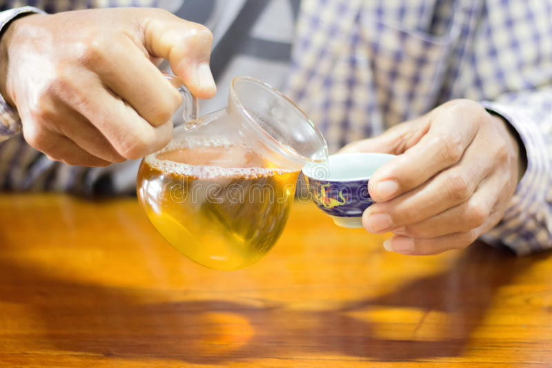Man pouring tea. To cup royalty free stock photography