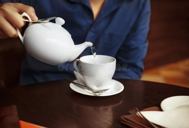 Man pouring tea into a white china tea cup stock images