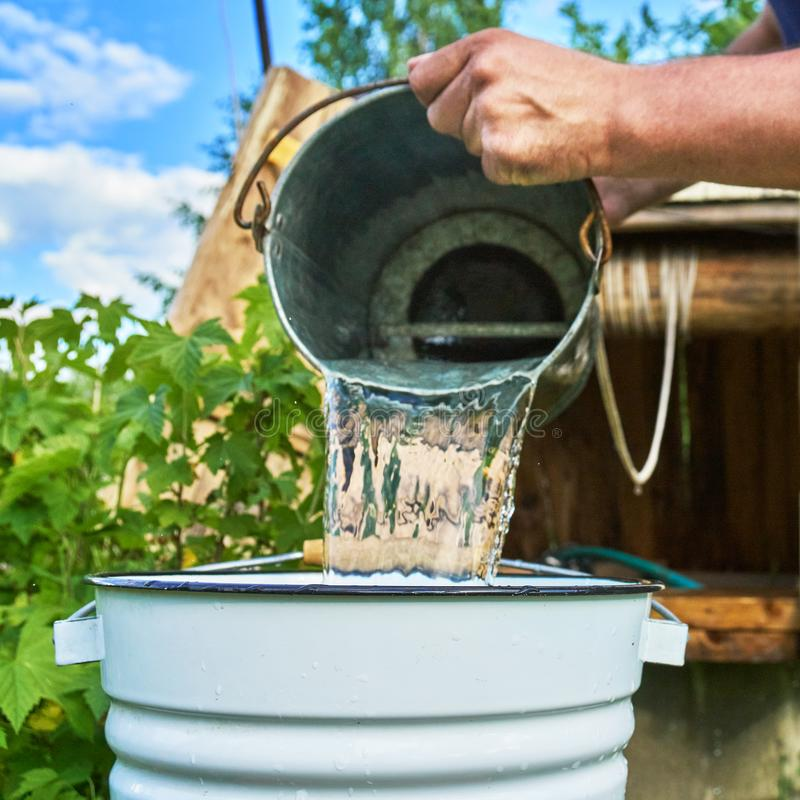 Man pouring water just taken up from a well into a enameled bucket royalty free stock images