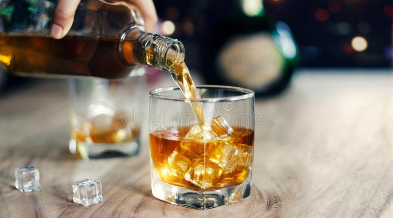 Man pouring whiskey into glasses, drinking alcoholic beverage royalty free stock images