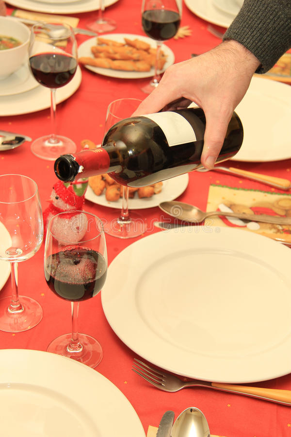 Man pouring wine at Christmas table stock photo