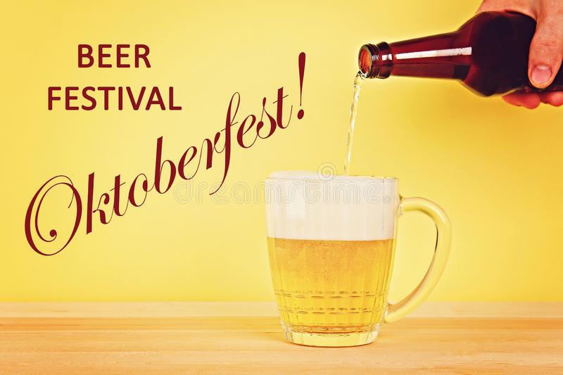 A man pours beer into a mug from a bottle on a yellow background on a wooden table. Octoberfest. A man pours beer into a mug from a bottle on a yellow stock photos