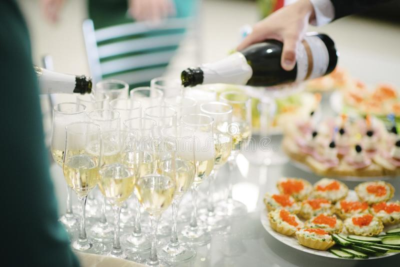 Man pours champagne into a glass from a bottle. Man pours champagne into a glass close up, alcohol, hand, restaurant, wine, background, drink, celebration stock photo