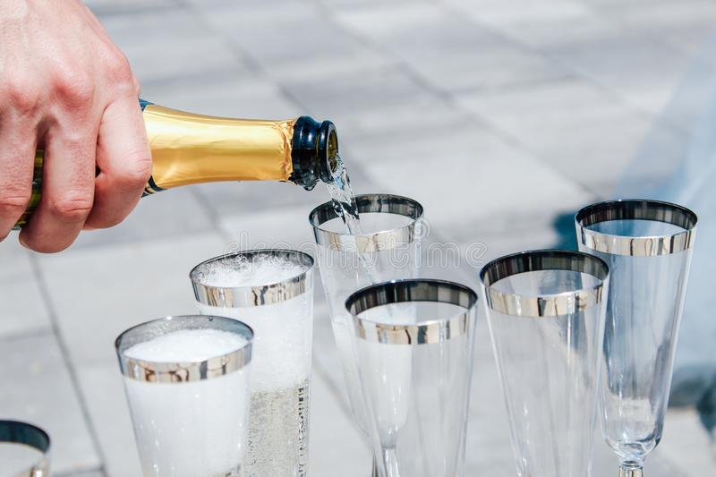 Man pours champagne into glasses. close-up royalty free stock photography