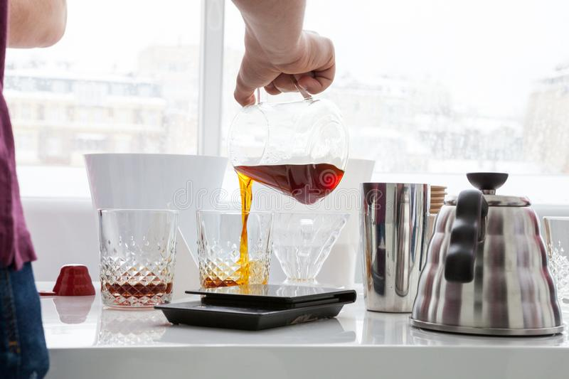 A man pours a drink. A man pours coffee for a sample from a decanter into faceted transparent glasses stock image