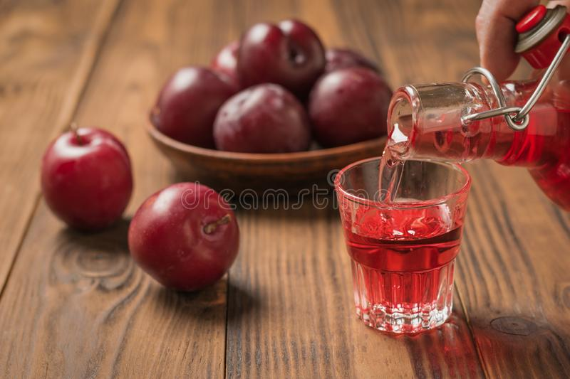 A man pours a glass of plum liqueur on a wooden table. royalty free stock image