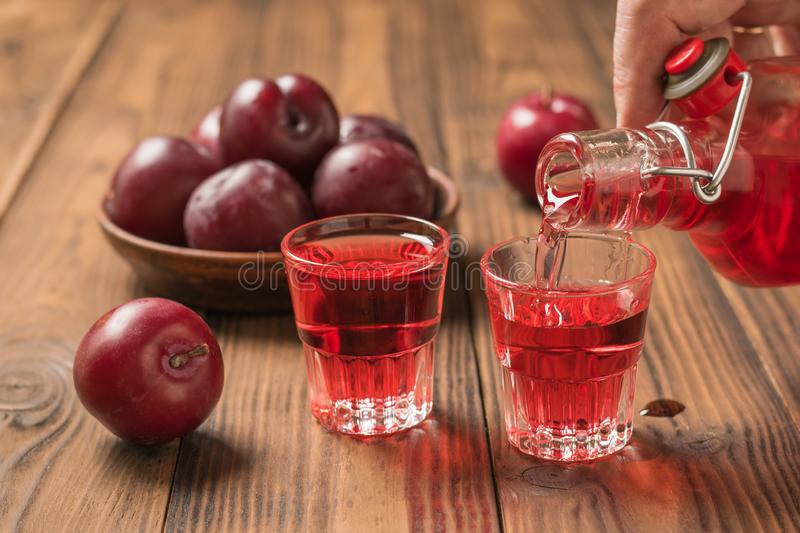 A man pours his right hand home plum alcohol. Homemade alcoholic drink made from berries plum royalty free stock photos