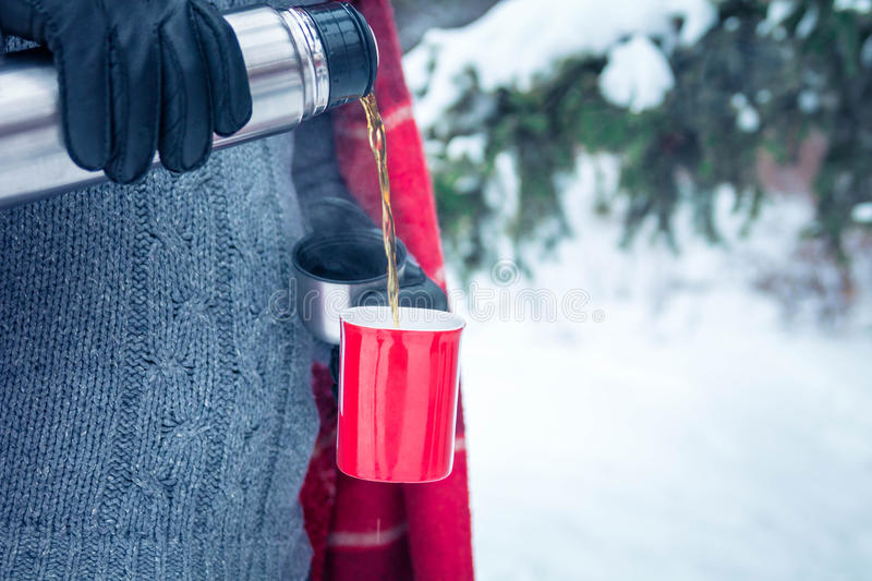 Man pours hot tea out of thermos in forest. Man pours hot tea out of thermos in winter forest stock photography