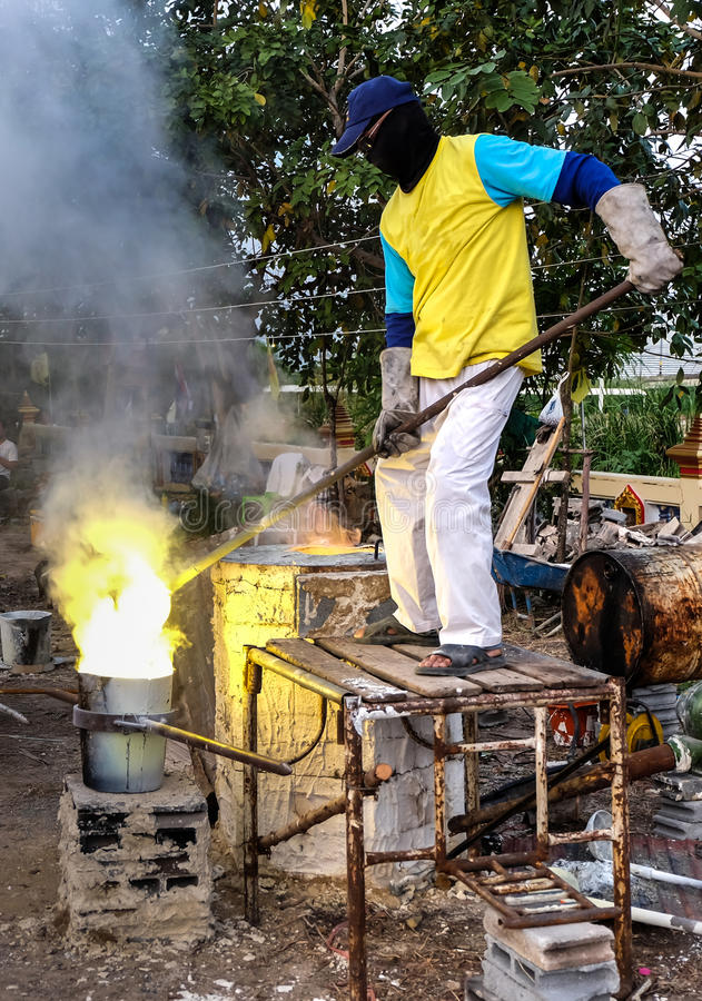 Man pours molten brass into a mold. royalty free stock photo