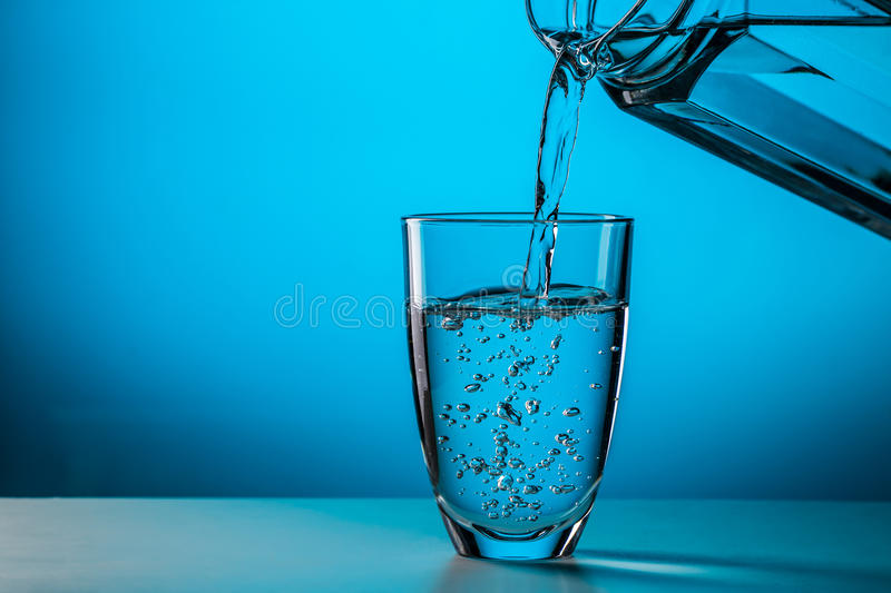 Man pours water from glass. Into glass on blue background in studio stock images