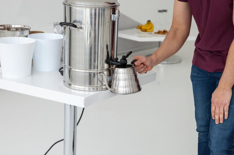 Man pours water. A person gently pours hot water into a metal kettle royalty free stock photo