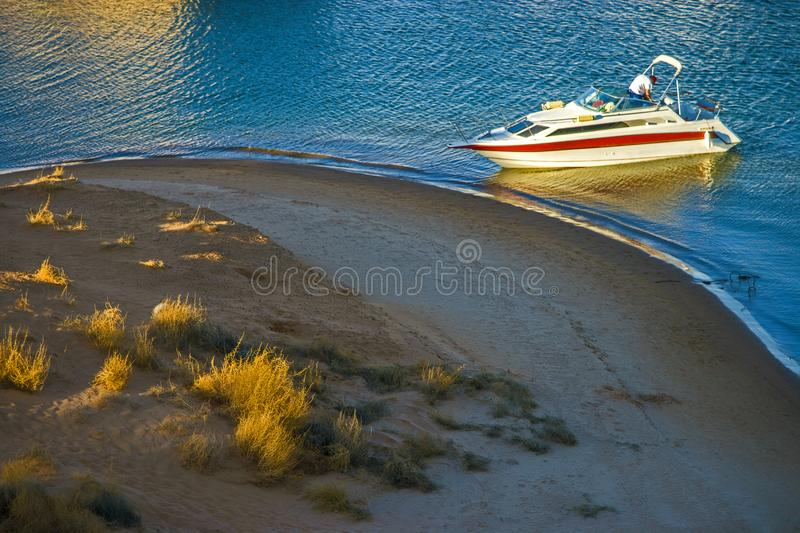 MAN ON POWER BOAT AT WATER EDGE BY BEACH IN LATE SUNSET. Man on power boat at water edge by beach and strong late sunset royalty free stock photos