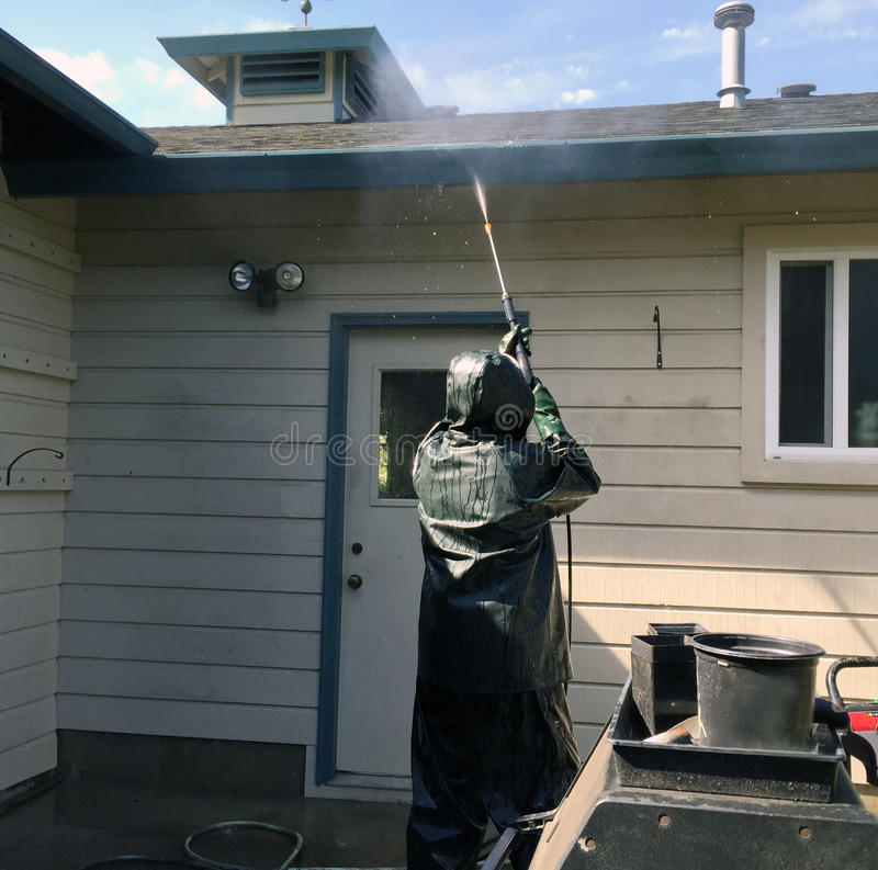 Man power washing a home. Man power washing a home, wearing rain gear on a sunny day stock images