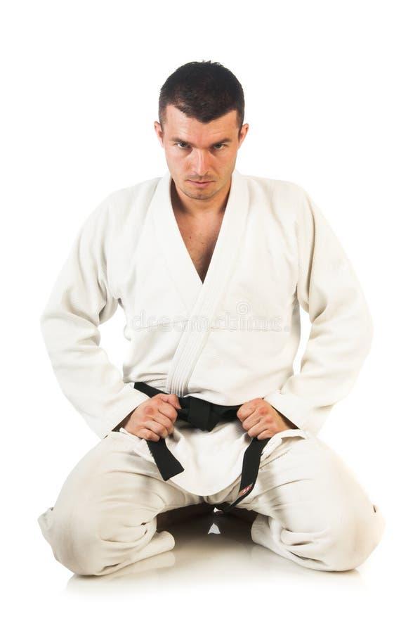 Man practicing Brazilian jiu-jitsu (BJJ). Young man practicing Brazilian jiu-jitsu (BJJ) isolated on white background stock photography