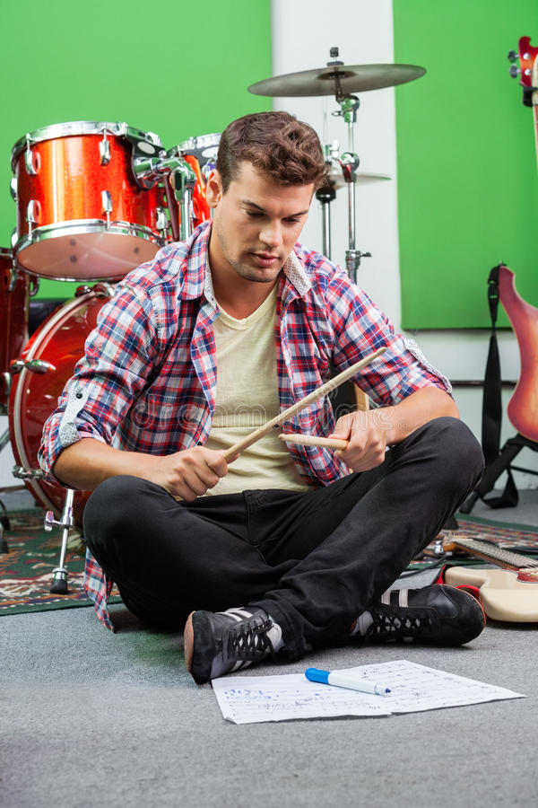Man Practicing With Drumsticks While Sitting On Floor. Full length of young man practicing with drumsticks while sitting on floor in recording studio stock image
