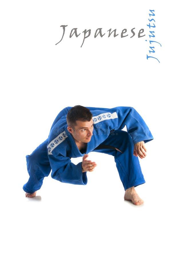 Man practicing jiu-jitsu. Young handsome man practicing jiu-jitsu (Hakki Heysen Ryu school) isolated on white background stock photos