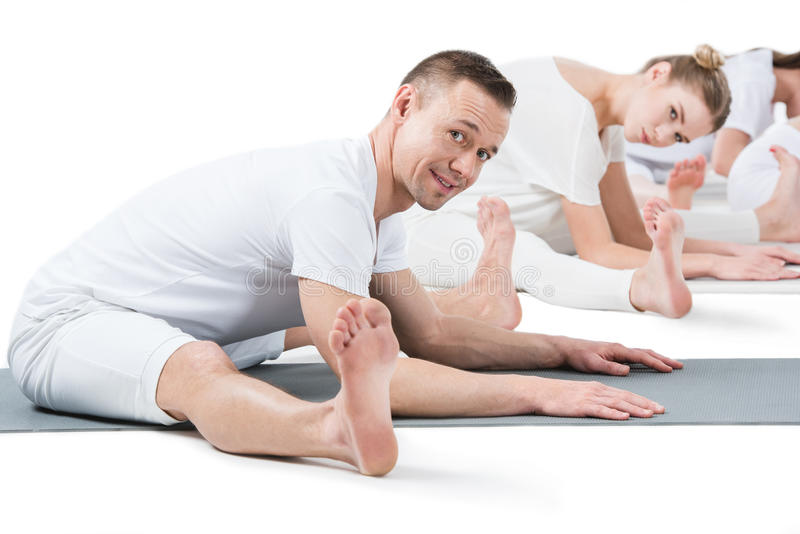 Man practicing Paschimottanasana pose and looking at camera with women behind royalty free stock photo