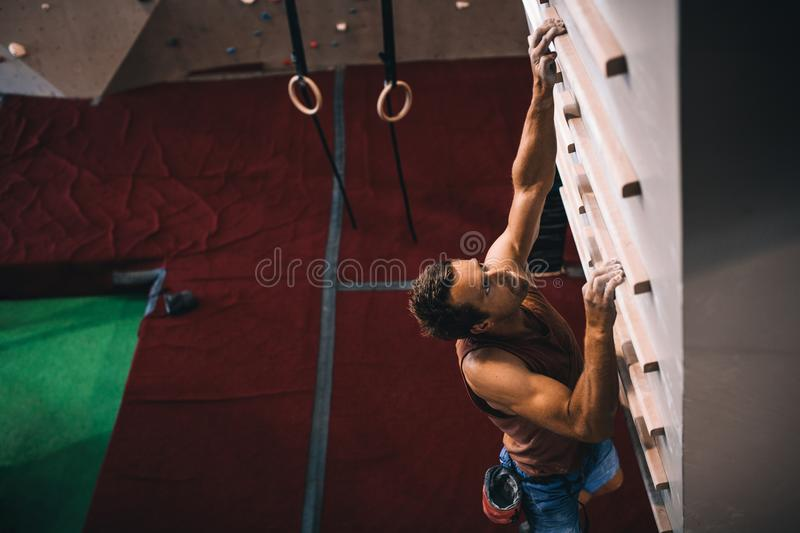 Man training on a campus board. Man practicing wall climbing on a campus board. Man climbing on a campus board at a wall climbing gym royalty free stock photo
