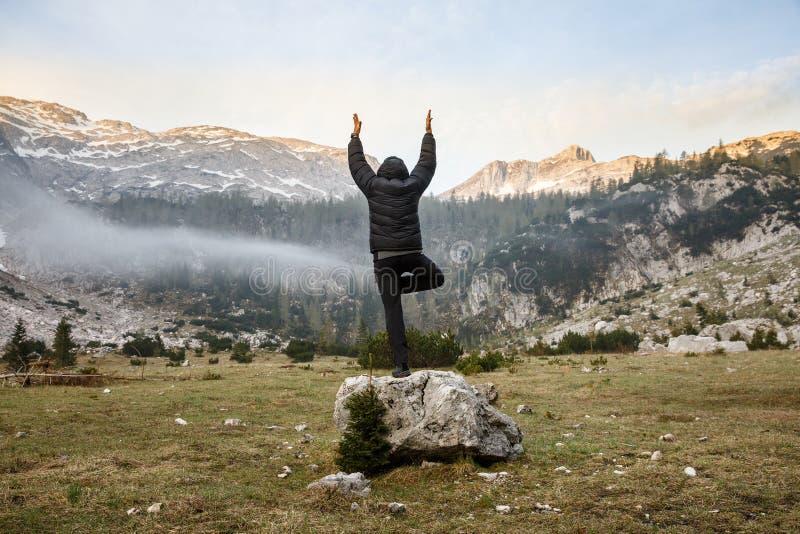 Man practicing yoga, performing a tree pose. Man practicing yoga, greeting the sun, performing a tree pose (vrksasana) in morning in beautiful mountain landscape stock image