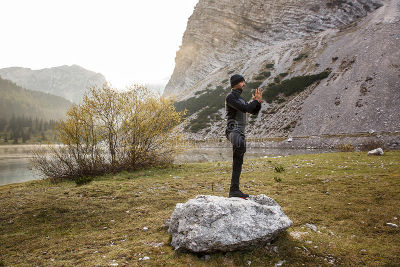 Man practicing yoga, performing a tree pose. Man practicing yoga, greeting the sun, performing a tree pose (vrksasana) in morning in beautiful mountain landscape stock photography