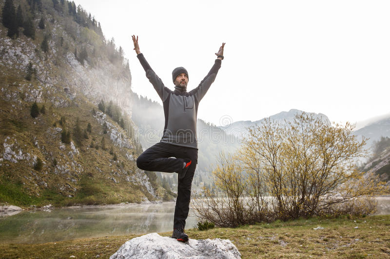 Man practicing yoga, performing a tree pose. Man practicing yoga, saluting the sun, performing a tree pose (vrksasana) in morning in beautiful mountain landscape stock photography