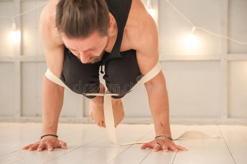 Man practicing yoga with a rubber band in the studio close-up. Meditation, yoga, asanas, relaxation.  stock photo