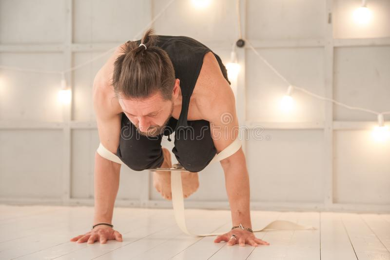 Man practicing yoga with a rubber band in the studio close-up. Meditation, yoga, asanas, relaxation.  royalty free stock photo