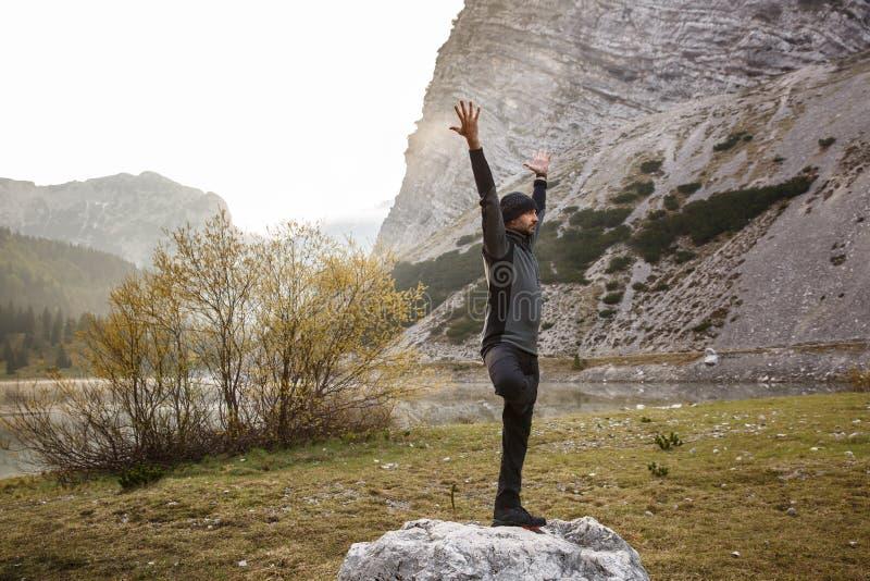 Man praktiserande yoga som utför ett träd, poserar royaltyfri fotografi
