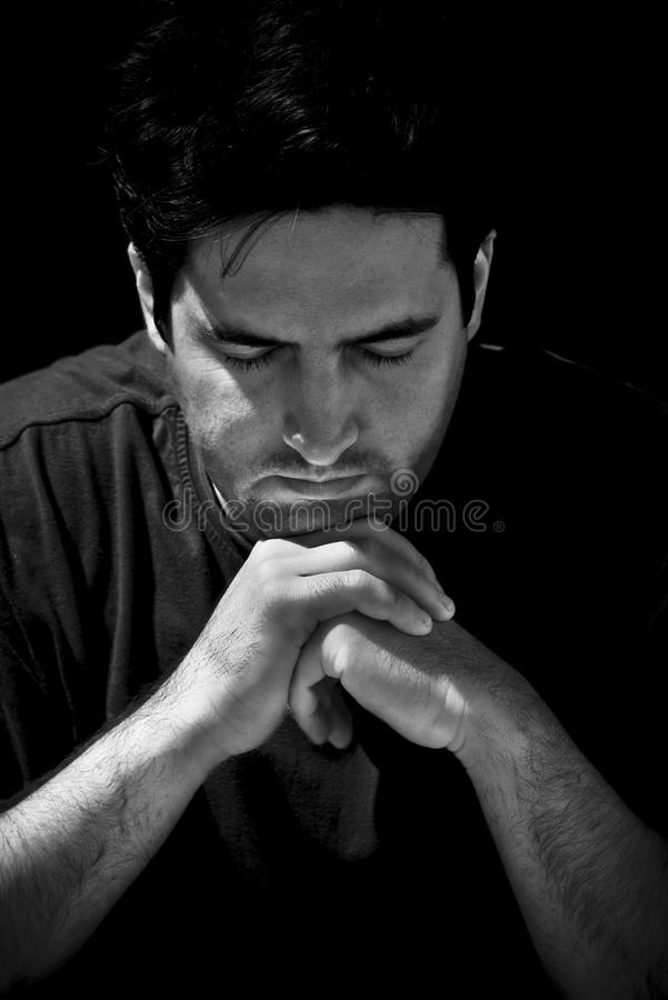 Man in prayer. A young man clenches his hands in prayer royalty free stock image