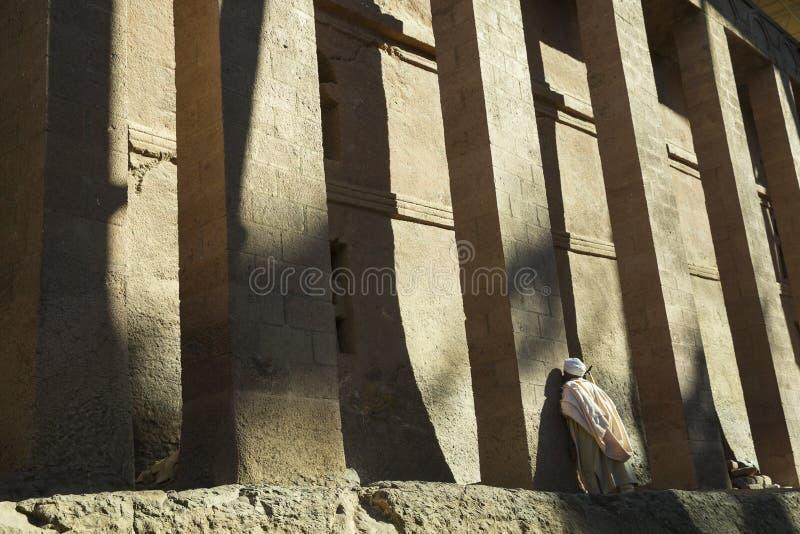 Man praying against pillar. Rock hewn church, Lalibela royalty free stock photo