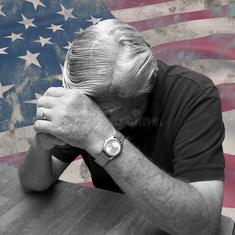 Man Praying For America. Patriotic image of man worried and praying for America with old and worn flag in background stock photography