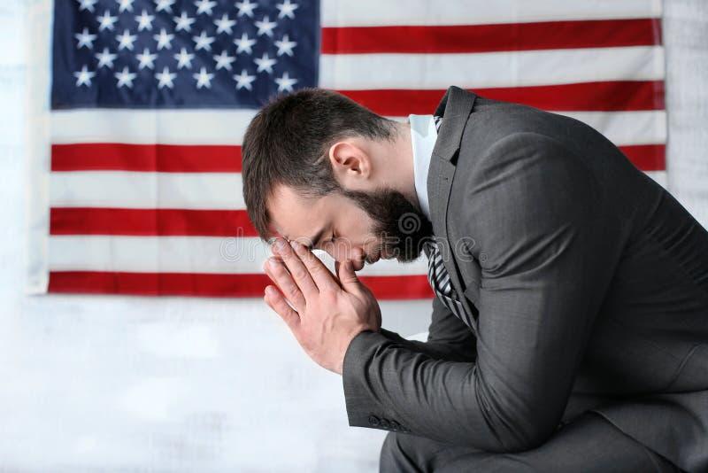 Man praying on American flag. Background stock photos