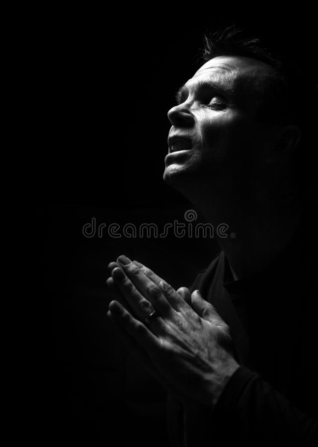Man Praying. A black and white image of a man kneeling down praying to God stock image