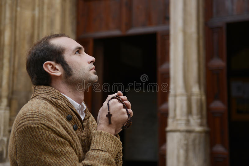 Man praying in church holding prayer beads stock photos