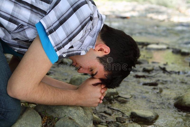 Man Praying By Creek Stock Image