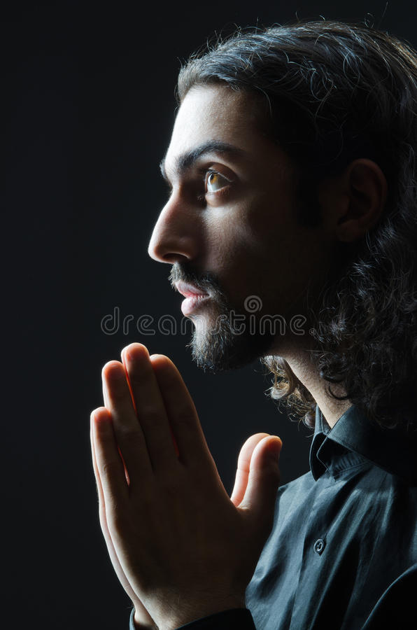 Man praying in darkness. Young man praying in darkness royalty free stock images