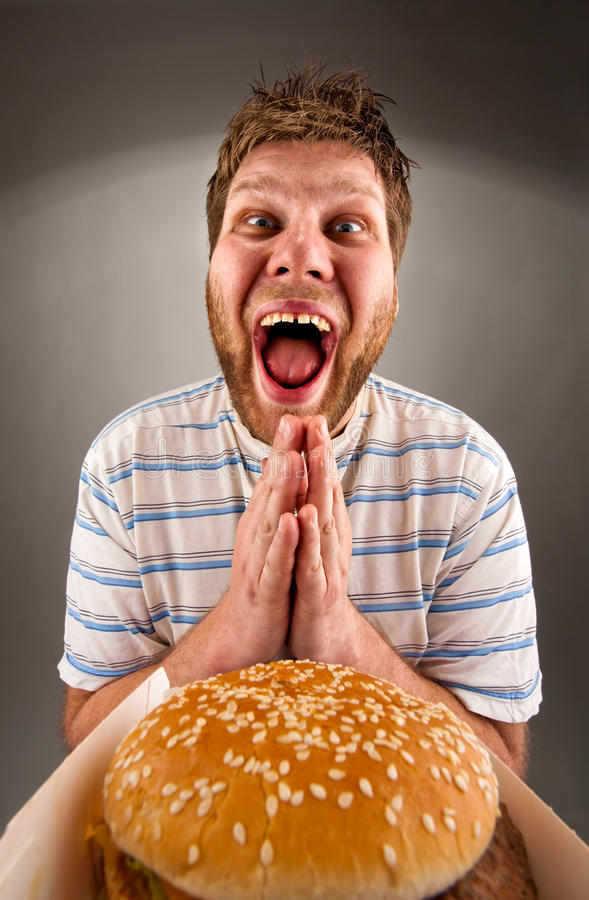 Man praying for fast food. Portrait of happy man praying for fast food royalty free stock photography