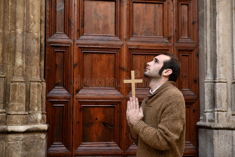 Man praying in front of the church holding a cross. Man or monk praying in front of the church holding a cross stock photography