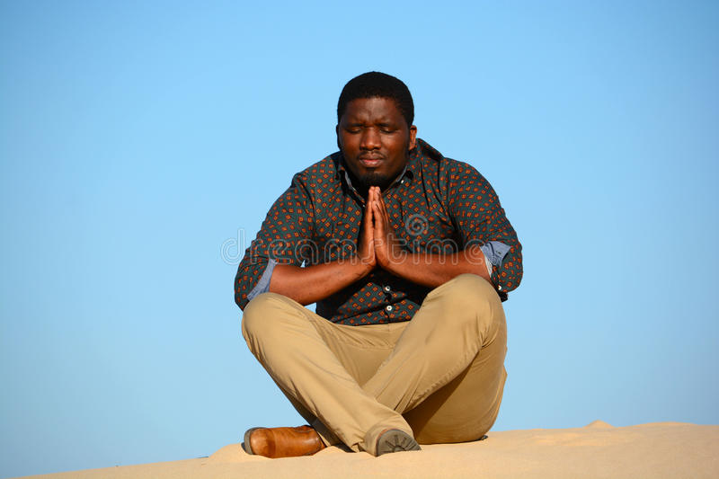 Man praying. Full body front view of a sitting African American man praying with closed eyes in front of blue sky background royalty free stock images