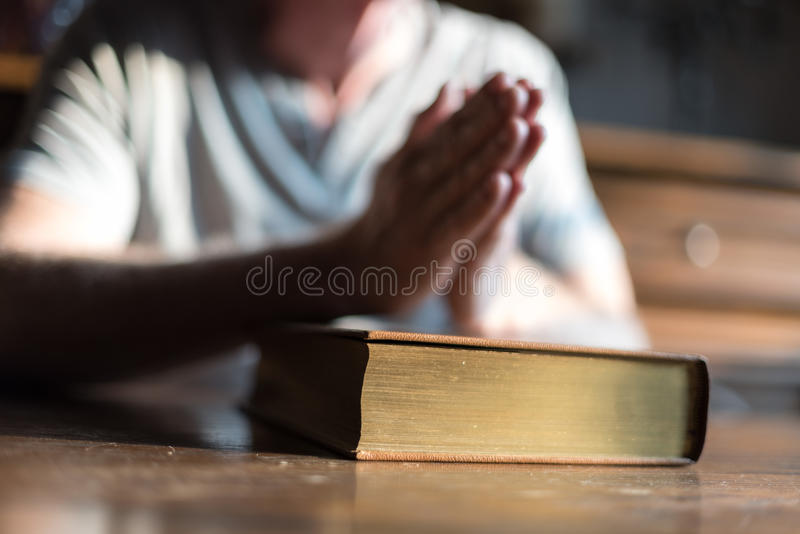 Man praying hands on a Bible. Man sitting at a table praying hands on a Bible stock photos