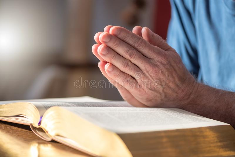 Man praying with his hands over the bible. Close up of man praying with his hands over the bible stock image