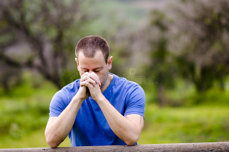 Man praying with his head down outside in nature. Man praying with his head down and hands together, alone in nature embracing God`s creation stock photos