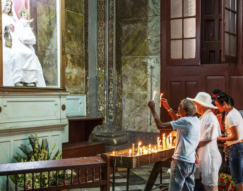 Man praying holding candles up to our lady in church in Cuba royalty free stock photography